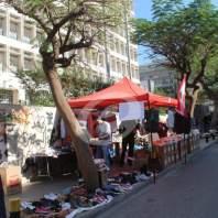 شباب وشابات يوزعون مواد غذائية امام مصرف لبنان - محمد عمر
